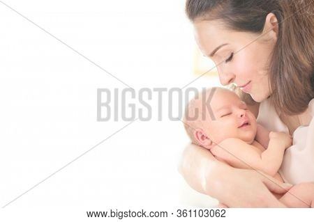 Mother and her Newborn Baby together. Love. Happy Mother and Baby kissing and hugging. High key soft image of Beautiful Family. Maternity concept. Parenthood. Motherhood, adoption concept