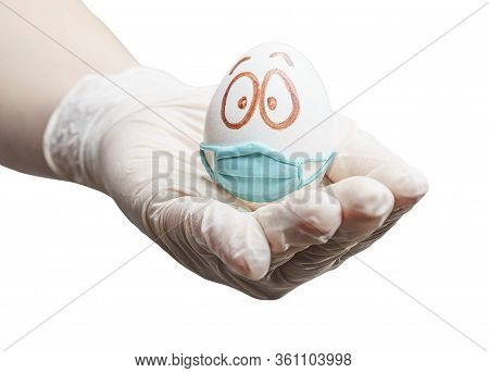 A Gloved Hand Holds An Egg In A Protective Mask. Concept - Isolation, Holiday Without Leaving Home