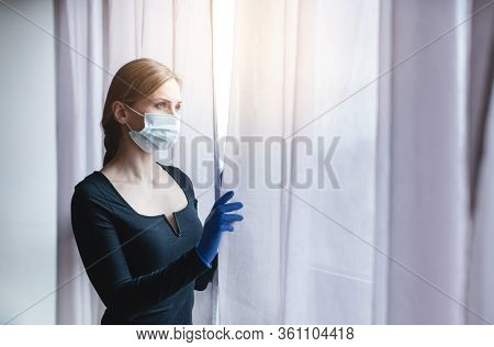 Bored woman in corona quarantine or under curfew looking out of window to the street