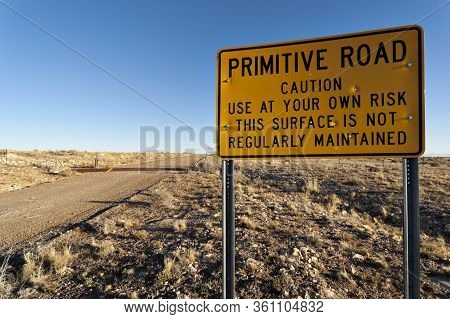 Primitive Road Caution Sign Next To A Dirt Road