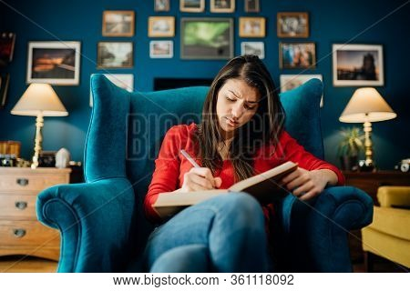 Woman Reading/studying A Foreign Language From A Book At Home.highlighting/underlining Difficult Lit