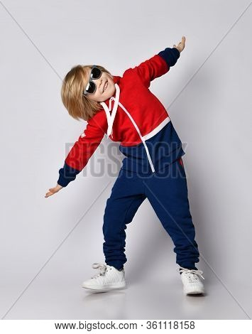Joyful Active Frolic Blond Kid Boy In Blue And Red Hoodie, Pants And Sunglasses Is Playing Aircraft