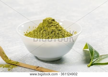 Close-up White Bowl Full Of Green Japanese Matcha Tea Powder, Special Wooden Bamboo Spoon And Fresh