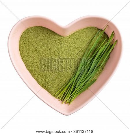 Organic Wheatgrass Powder In Heart Shaped Bowl Isolated On White Background. Top View, Close-up.  Gr