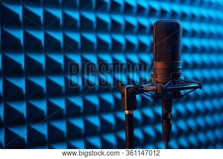 Studio Condenser Microphone On Blue Acoustic Foam Panel Background