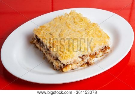 Beef Lasagna Or Lasagne Topped With Grated Parmesan And Tomato Sauce On White Plate.
