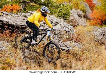 Woman Rider Riding On Autumn Trail In Downhill Race