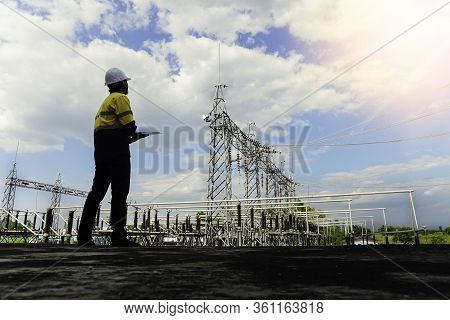 A Low-angle View Of The Engineer Looking At The Drawing Of A Small Size Power Plant To Verify Instal