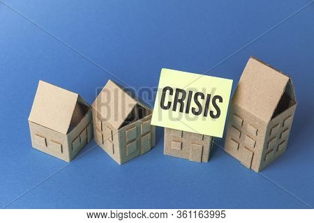 Cardboard Toy Houses On Blue Background With Crisis Sign. Falling Property Prices. Economic Depressi