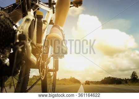 Shot From The Back Of A Bicycle With A Boy Riding On A Bicycle On The Public Road In The Summer As A