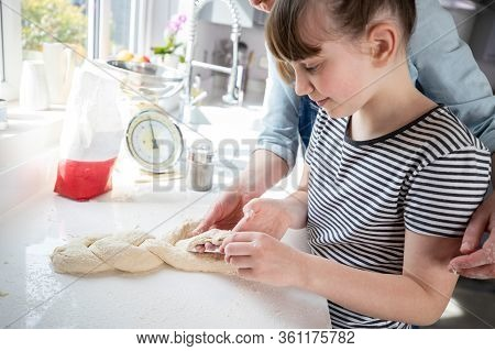 Mother And Daughter Having Fun In Kitchen At Plaiting Dough For Home Baked Bread Together