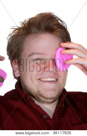 Smiling Teen Boy Removing Pink Marshmallow Hearts From Eyes