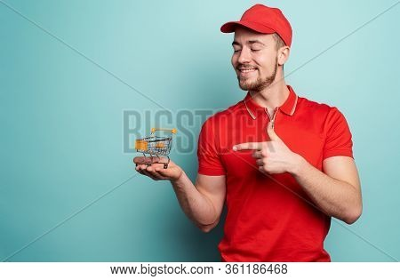 Deliveryman Shows The Cart Where To Buy. Cyan Background