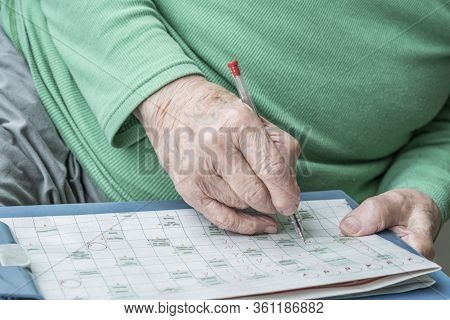 Closeup Wrinkled Hand Of A Senior Person Solving Crossword Puzzle