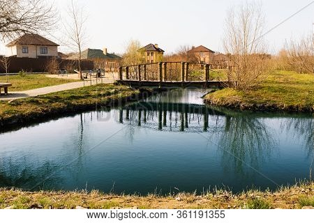 Blue Pond With Sky Reflection And Village Houses.wooden Bridge Over A Small River Or Pond, Side View