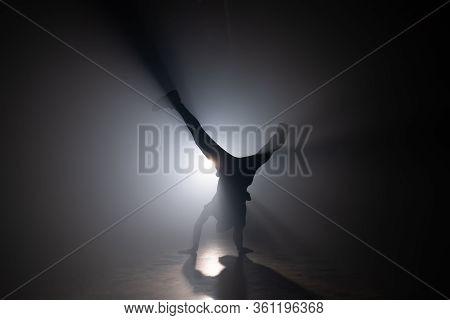 Silhouette Of Young Man Breakdancing, Training In Dark Smoky Studio. Street Hip Hop Dancer Performin