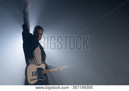 Rock Guitarist Man On Smoky Stage And Masterfully Playing Electric Guitar. View Of Musician Raises H