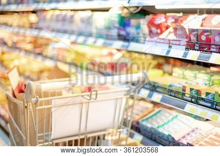 Blurred Effect In The Supermarket Aisle With Silver And Green Shopping Trolley,  Shopper Choosing Th
