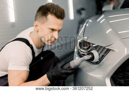 Detailing And Polishing Of Car Headlight On Car. Young Professional Concentrated Caucasian Male Work