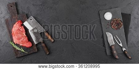 Raw Beef Slice On Chopping Board With Hatchets And Fork With Knife On Black Background With Salt And