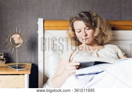 Young Eastern European Woman Reading A Book While Lying In Bed In The Morning.