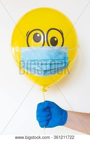 Hand In A Rubber Glove Holding A Yellow Balloon With A Medical Mask And Doodle Shocked Eyes. Concept