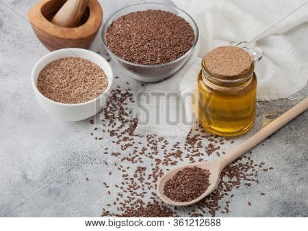 Bowl Of Raw Natural Organic Linseed Flax-seed With Spoon And Glass Jar Oil On Light Background With