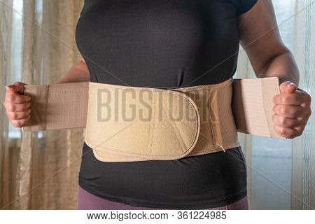 Housewife Wears A Lumbosacral Corset, A Wide Belt To Support The Back Muscles