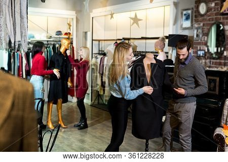 Young Woman And Man Shopping Warm Jackets At The Apparel Store. Shopping, Fashion, Clothes, Style An