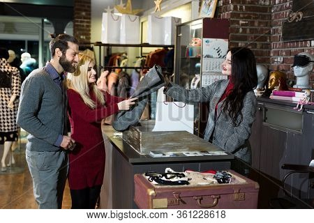 Smiling Couple Buying Clothes Together. Buying Pants For An Attractive Blonde.