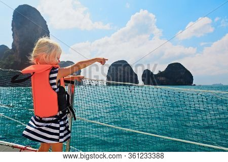 Happy Little Baby In Life Jacket On Board Of Sailing Boat Watching Offshore Sea And Tropical Islands