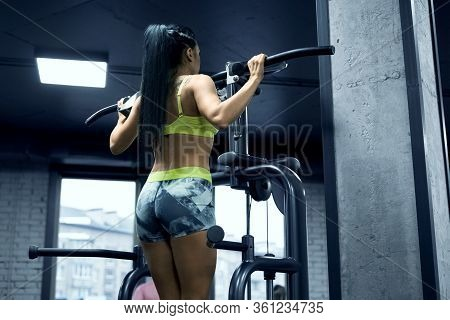 From Below View Of Young Fit Woman With Long Black Hair Doing Pull Ups On Gravitron Gym Machine In S
