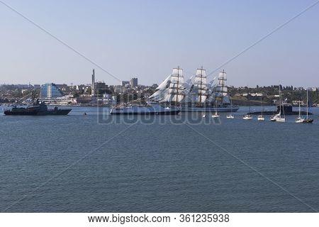 Sevastopol, Crimea, Russia - July 28, 2019: Khersones Sailboat Passes Near The Parade System Of Wars