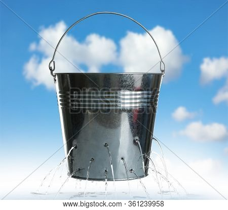 Leaky Bucket With Water Against Blue Sky