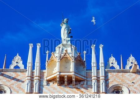 Huge Themis Statue. The magnificent facade of the Doge's Palace. Doge's Palace is a great monument of Italian Gothic architecture. Magical journey to Venice. The concept of photo tourism