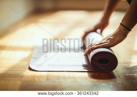 Close Up Of A Womans Hands Is Rolling Up Exercise Mat And Preparing To Doing Yoga. She Is Exercising