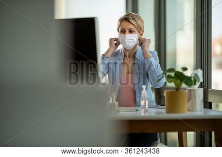 Business Woman In A Medical Protective Mask Works From Home At The Computer During Self-isolation An