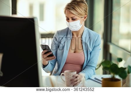 Business Woman In A Medical Protective Mask Surfing At Social Network At The Smartphone During Pause