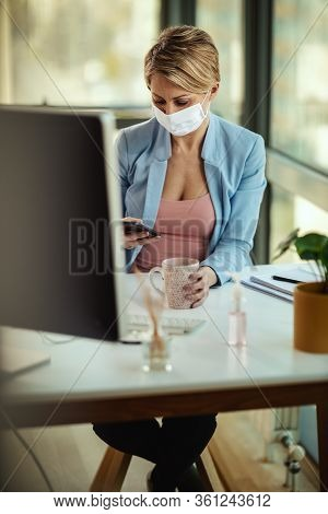 Business Woman In A Medical Protective Mask Using Smartphone And Works At The Computer During Self-i