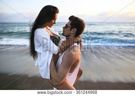 Beautiful, Sexy, Young Caucasian Couple Cuddling On The  Beach At Sunset Time Near Ocean  During Sum