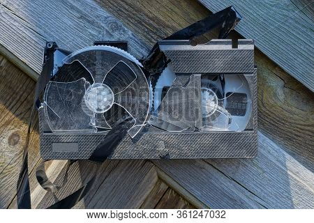 One Old Broken Plastic Video Cassette Is Lying On The Gray Wooden Boards Of The Table