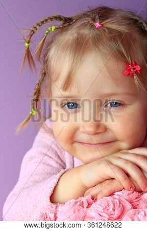 Portrait Of Little Girl With Pigtails. Baby Smiling. Three Years Girl Smiling Close-up. Portrait Of