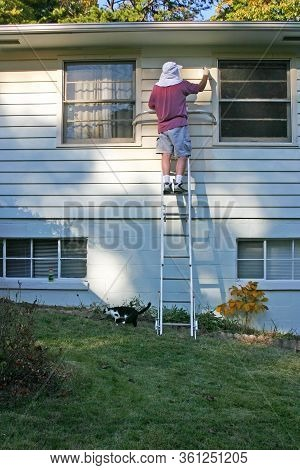 A Man Precariously Balances Atop A Ladder Set On An Incline As He Paints The Exterior Of A House On