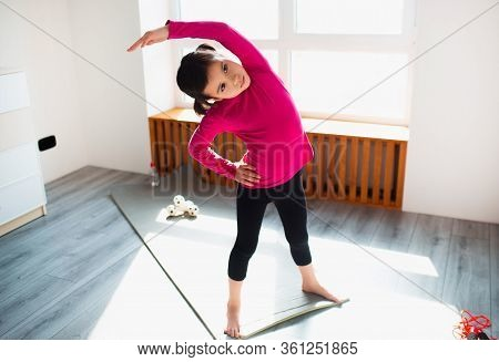 Little Girl Is Doing Back Tilt Standing Workout At Home. Cute Kid Is Training Onon A Mat Indoor Indo
