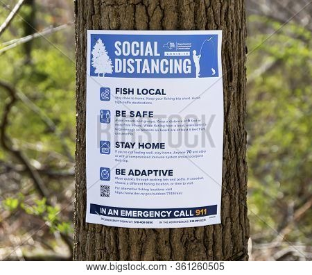 Babylon, New York, Usa - 1 April 2020: A Paper Sign Is Staples To A Tree In A Park Telling People To