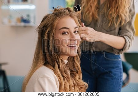 Beautiful lovely blonde woman with long hair sitting at the beauty salon, curling hair