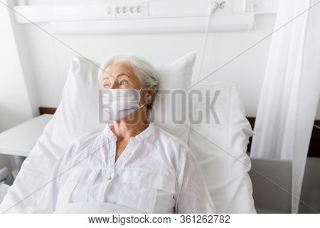 medicine, health safety and pandemic concept - senior woman patient lying in bed wearing face protective medical mask for protection from virus disease at hospital ward