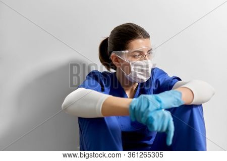 medicine, healthcare and pandemic concept - sad young female doctor or nurse wearing goggles and face protective mask for protection from virus disease sitting on floor at hospital