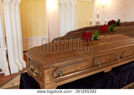 funeral and mourning concept - red rose flowers on wooden coffins in church