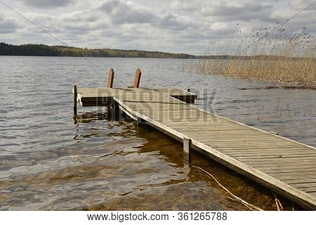 Southern Karelia, Finland, May, 10, 2014. Wooden Dock Near The Waterside With Cloudy Sky In Backgrou